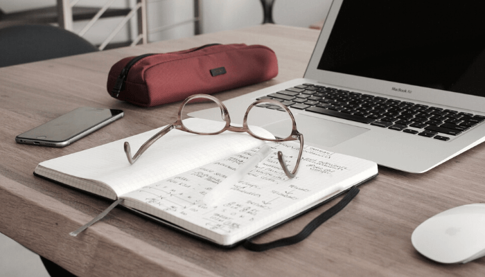 a desk with a laptop, book, mouse, glasses, phone and pencil case