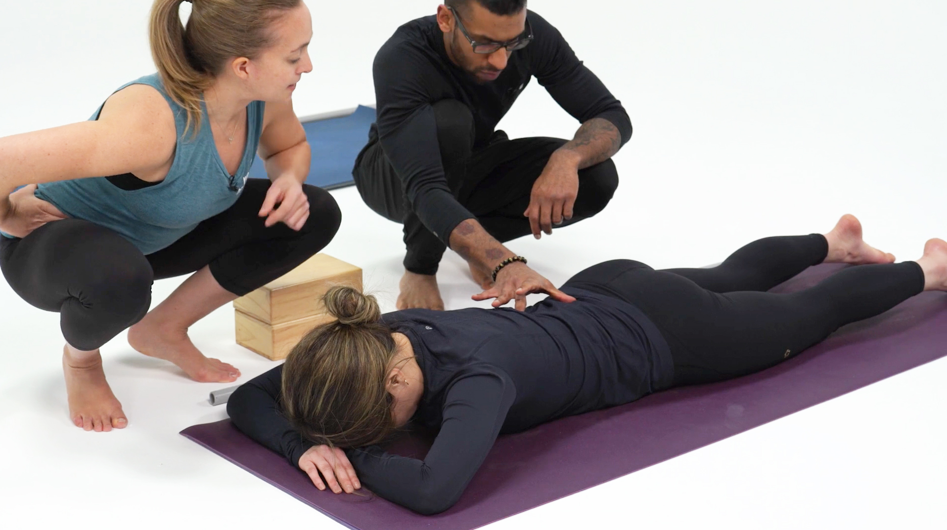 Screenshot of Cecily and person looking at someone's lumbar area while they lie prone