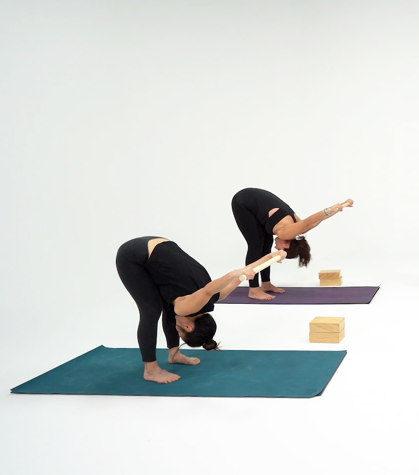 Two students leaning down while standing, their hands outstretched behind them with a yoga band between their hands.