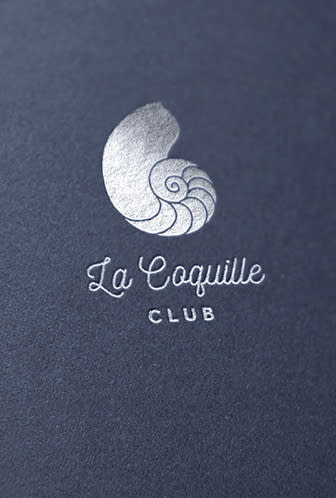 La Coquille Club logo printed on a blue surface.