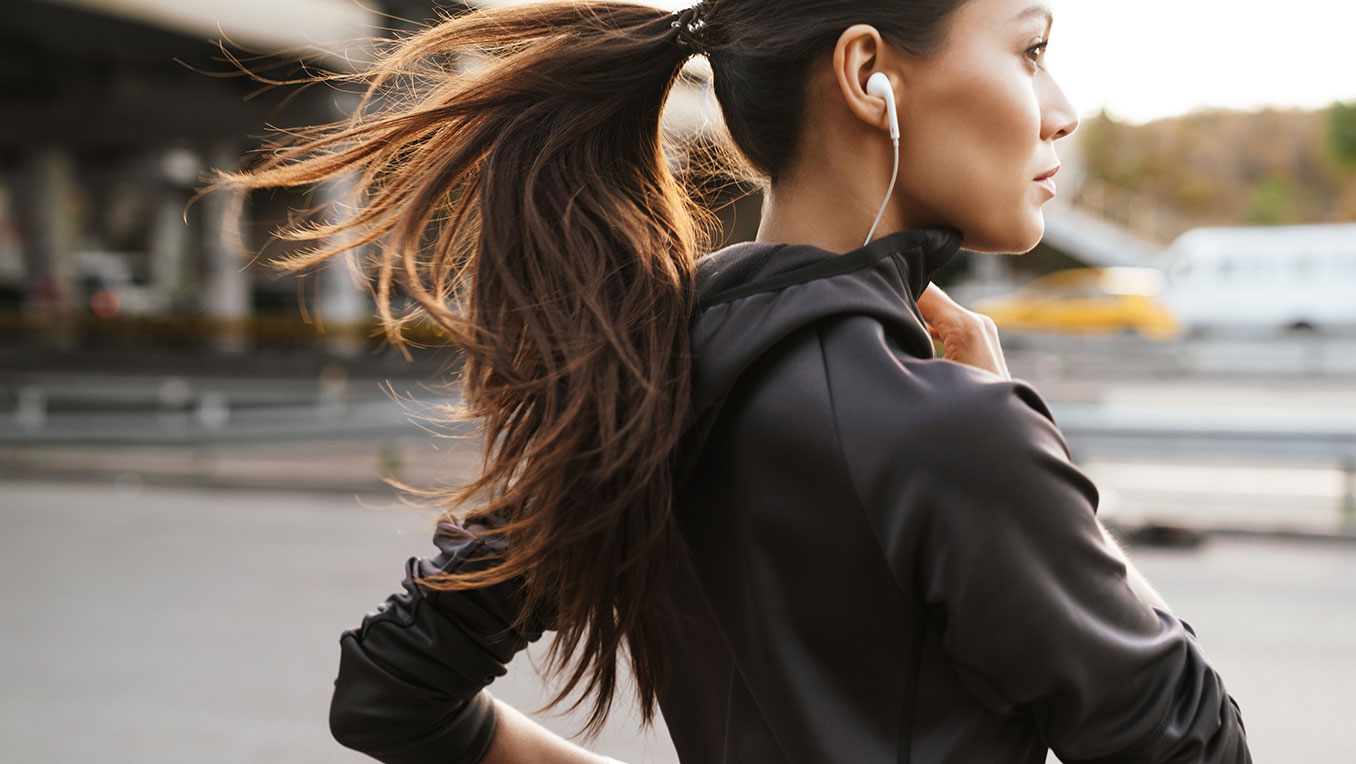 A woman of colour jogs through the city, listening to content with earbuds