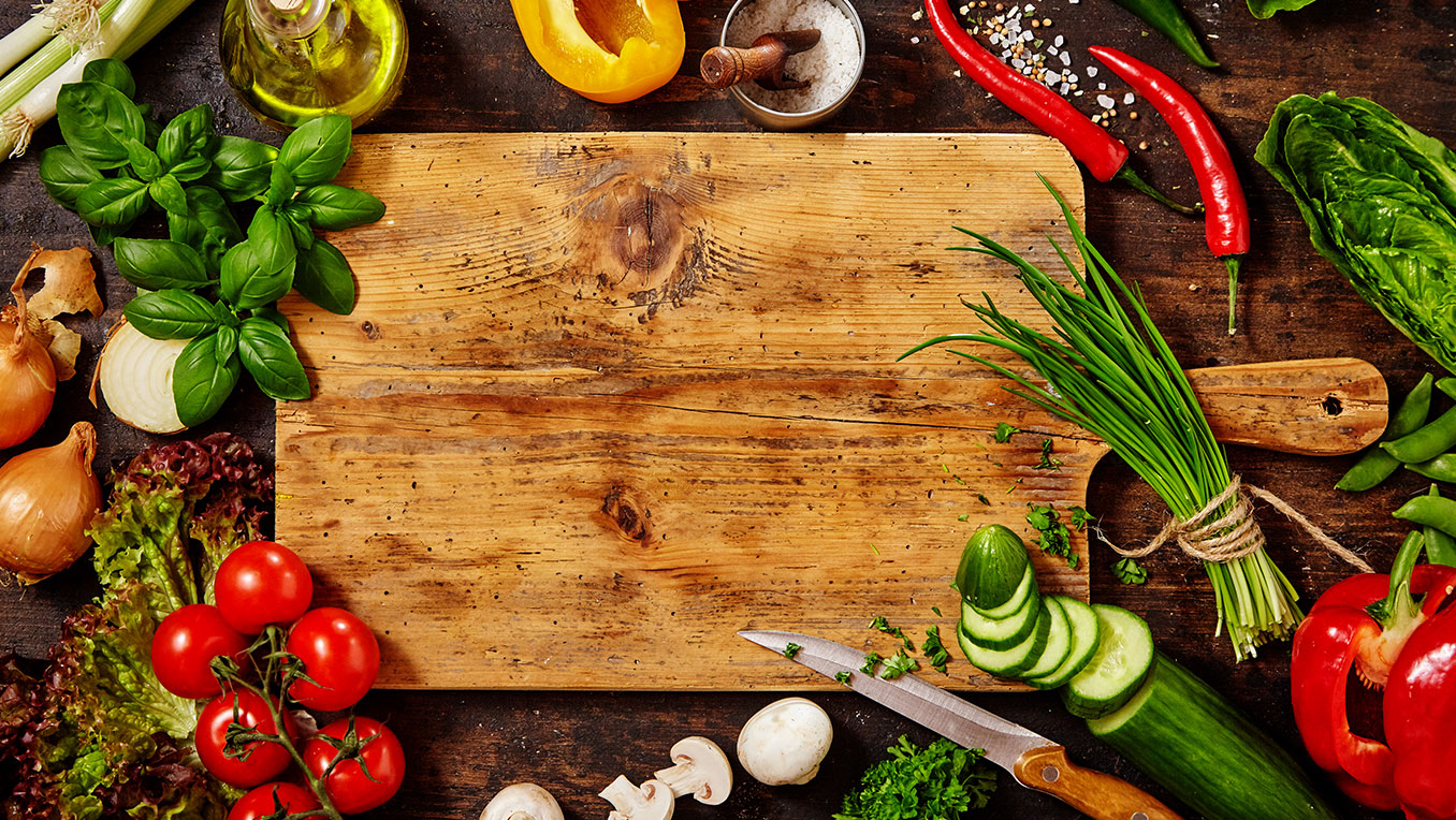 A top-down view of a wooden cutting board surrounded by vibrant vegetables