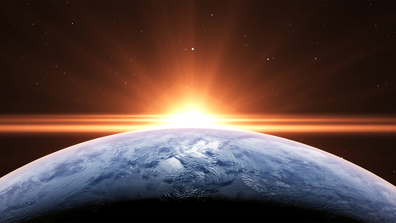 Wide angle image of the sun rising over the earth in space casting a bright horizon