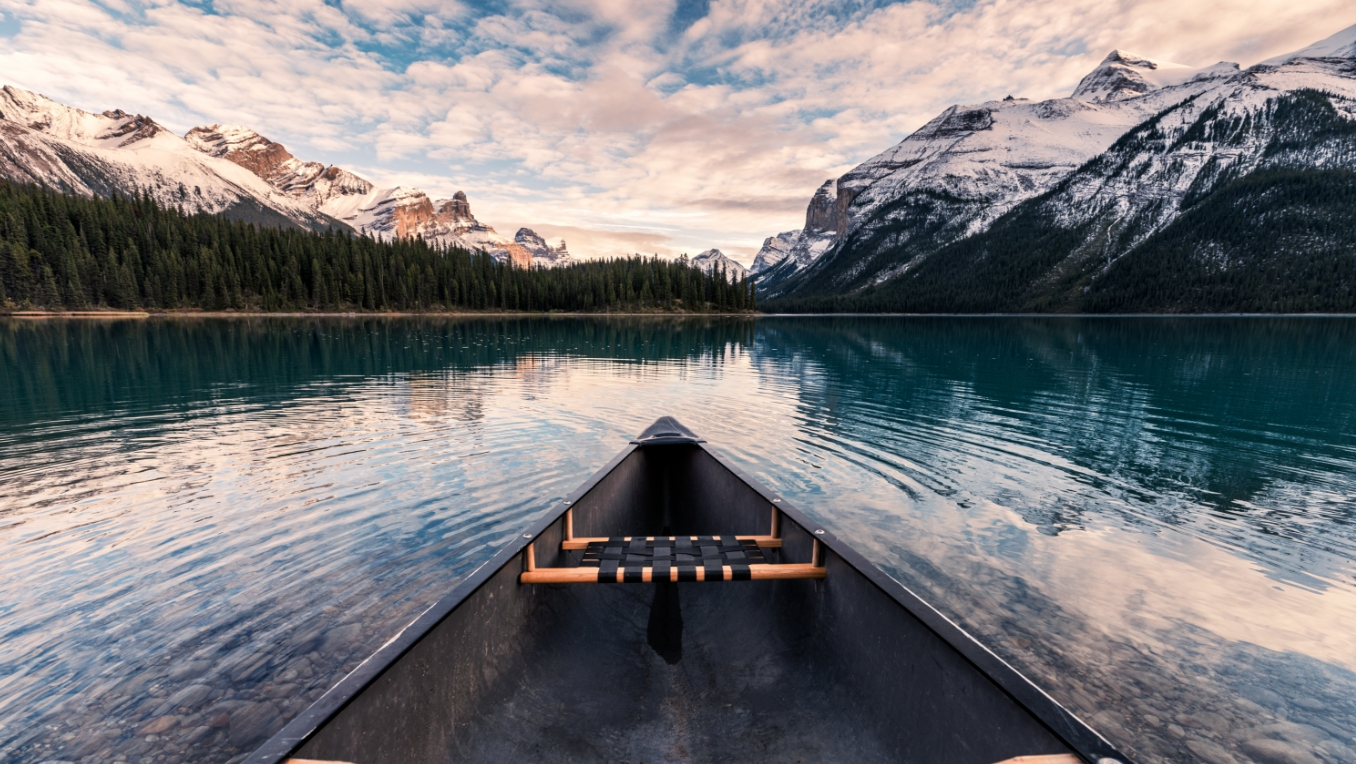 The image of a canoe on a tranquil lake near the mountains