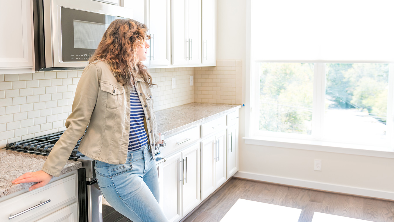 Young woman in jeans leans against a spotless kitchen counter and looks out the window.