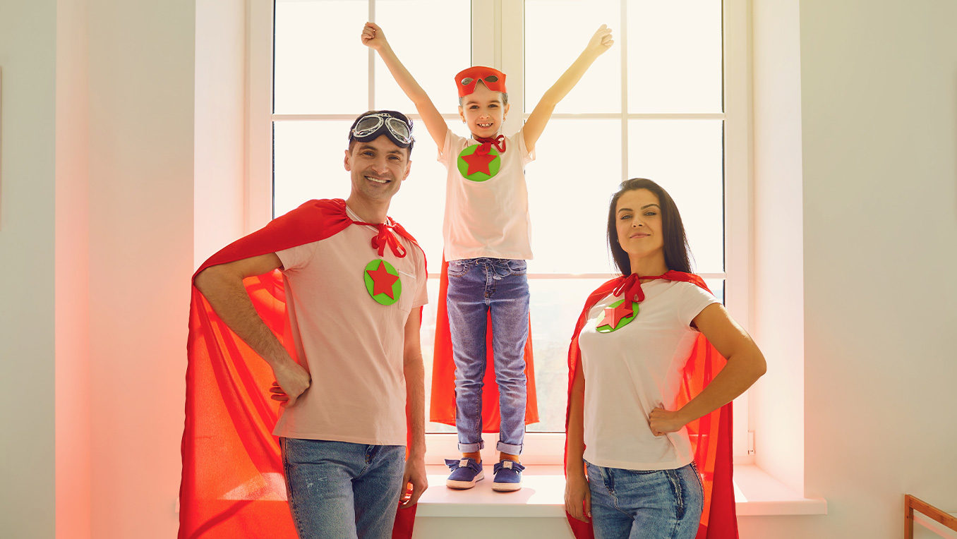Mom and dad wear red capes with their son while standing in front of a large window in their home dressed as super heroes