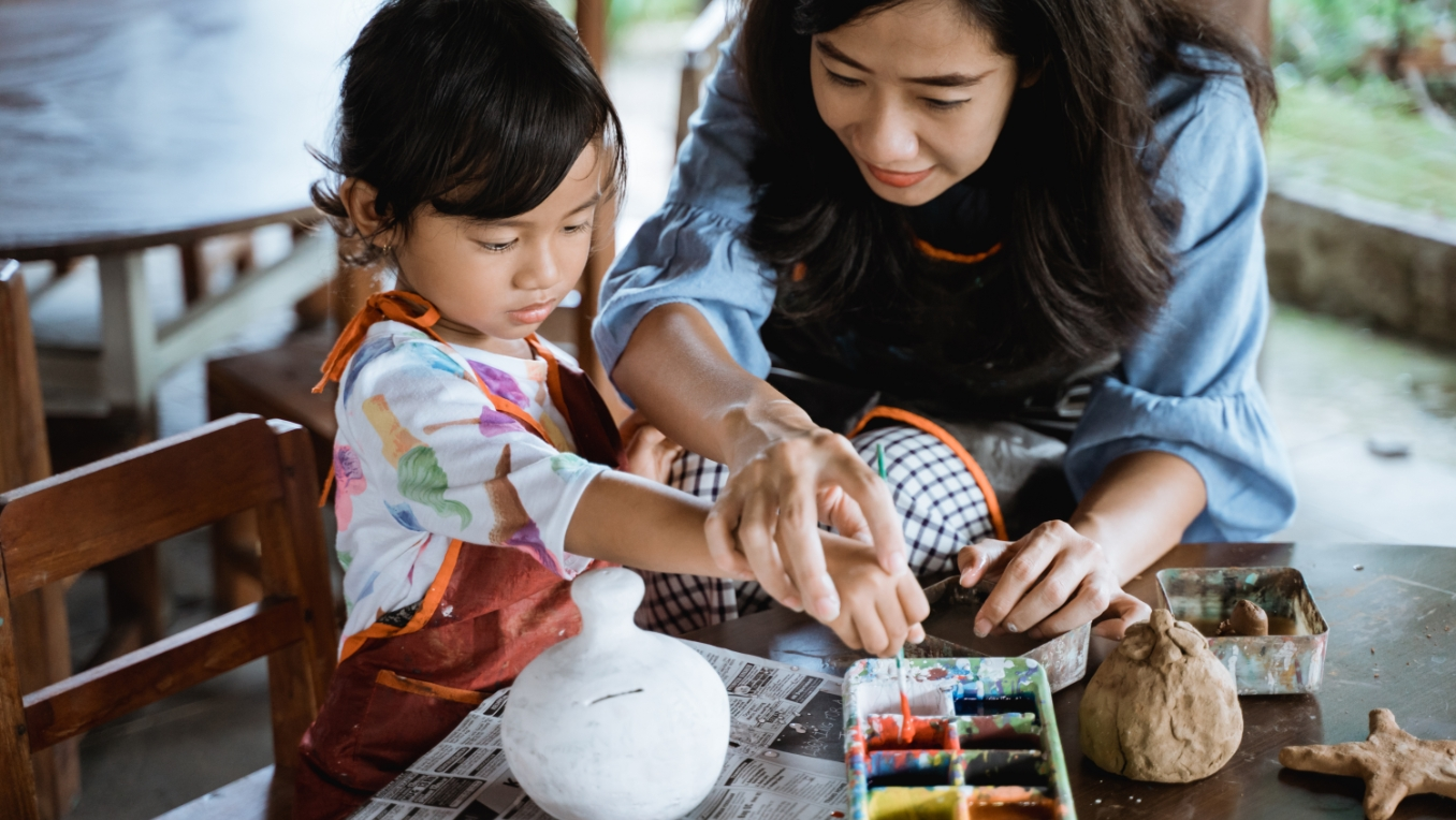 A mother and daughter paint pottery together at a wooden table