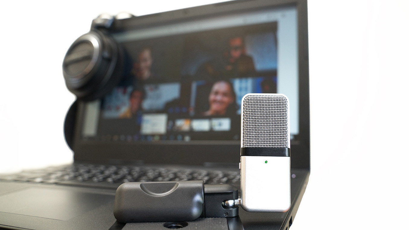A microphone set up in front of an online group video call