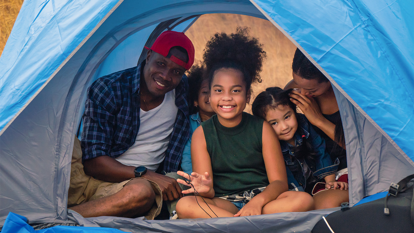 African-American family smiling inside a tent at a campground