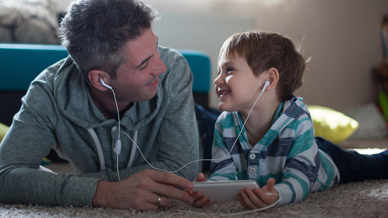 Father and son listen to bedtime stories with headphones lying on the floor of their house