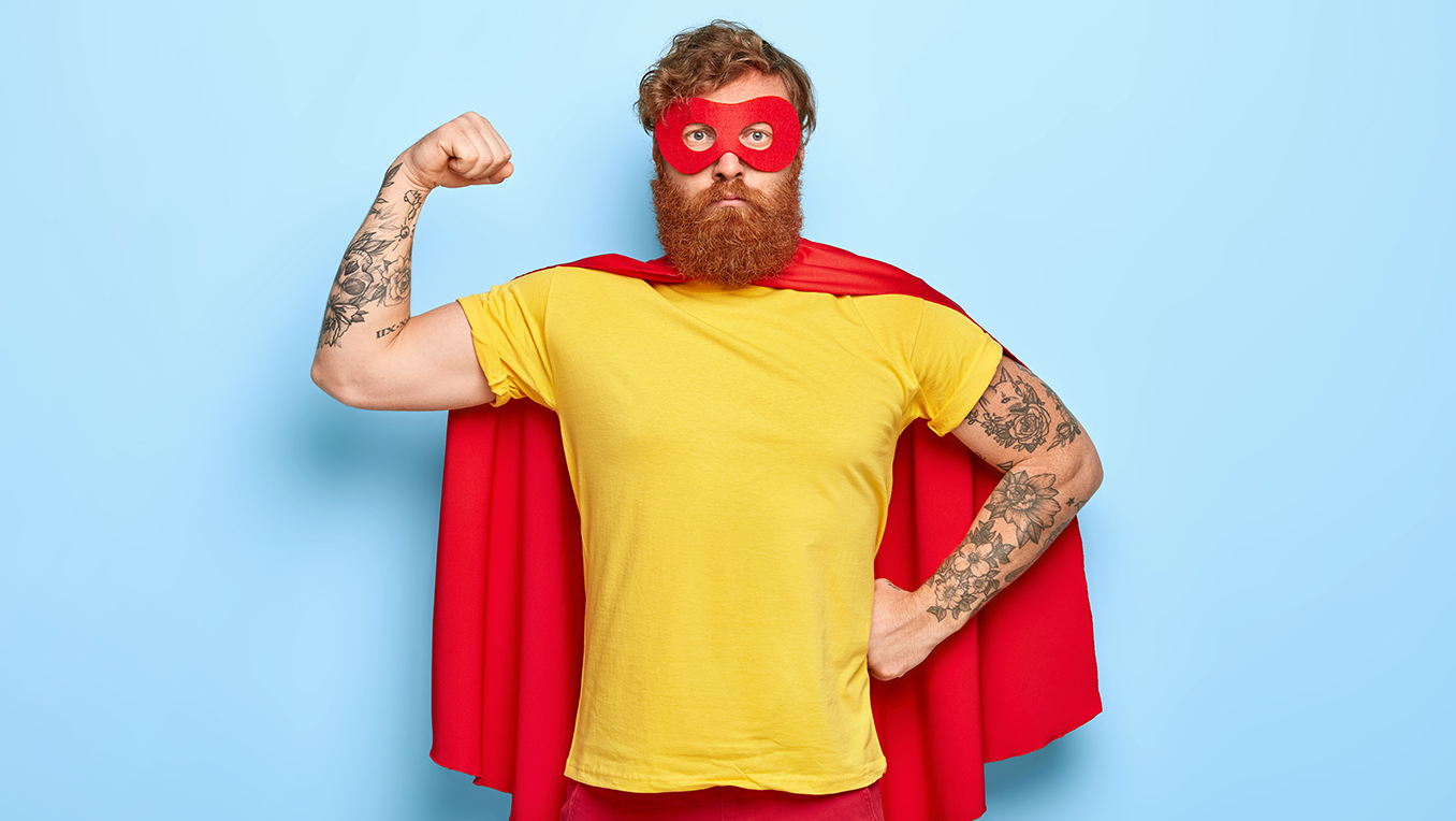 Bearded man wearing a red mask and red cape flexes his arm muscles in a super hero pose with a serious face