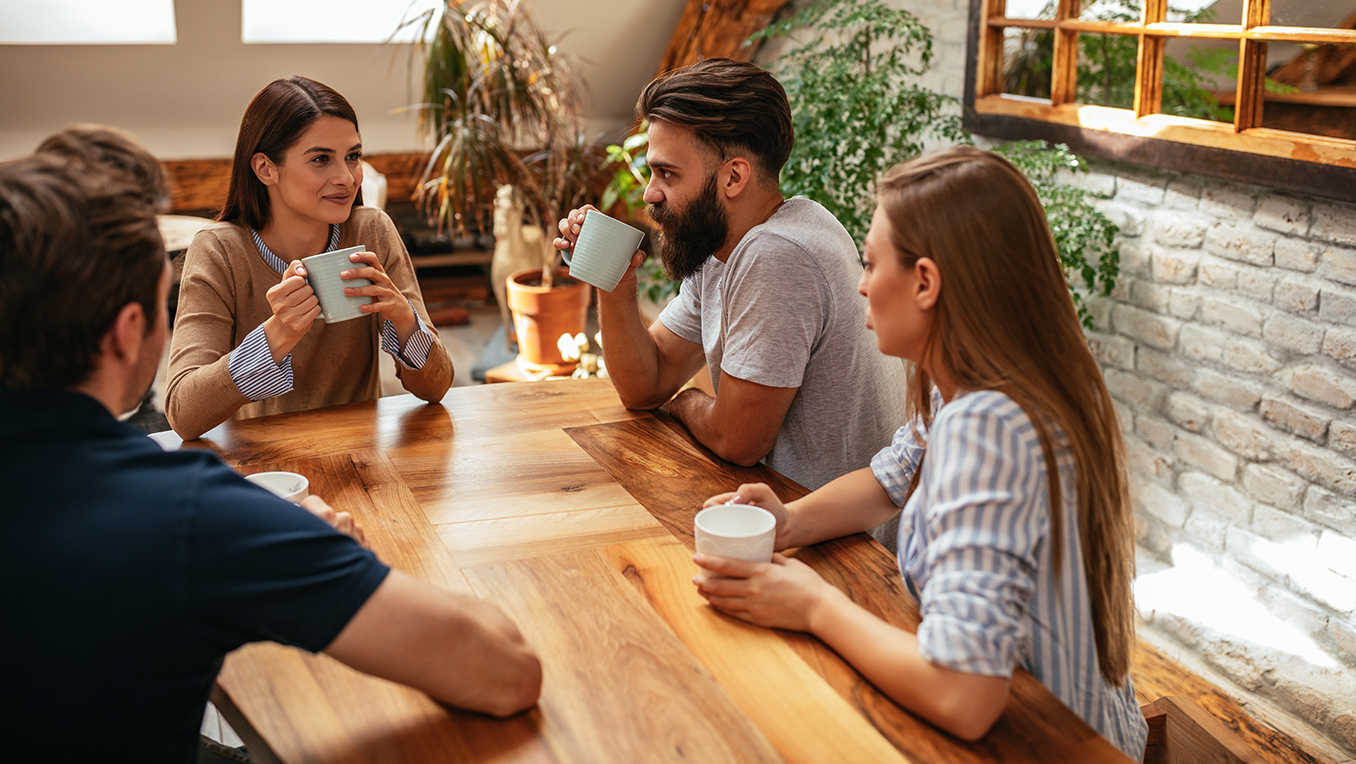Group of two males and two females sit at a wooden coffee table drinking coffee having a group discussion