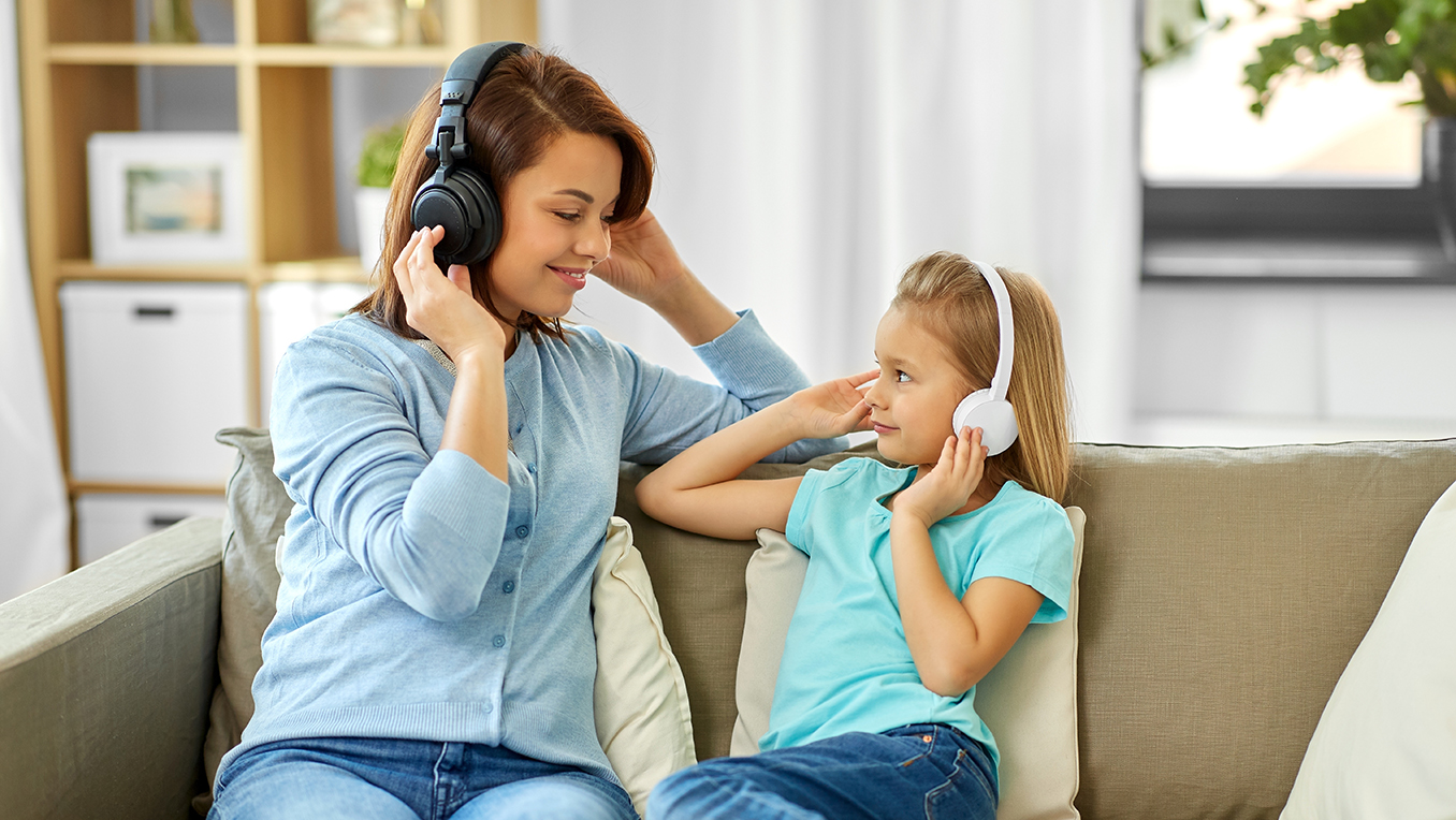 Mother and daughter sitting together on a sofa listening to a children's audiobook at home