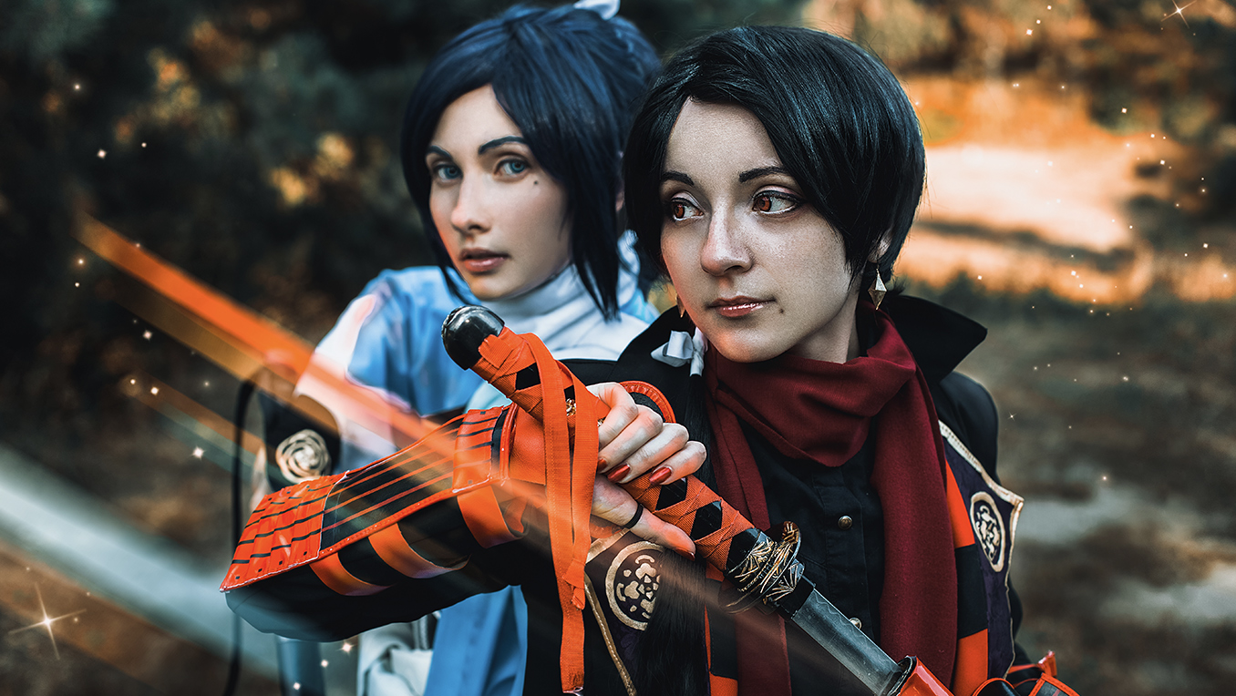 Two women cosplaying as futuristic samurai holding katanas, dressed in orange and blue