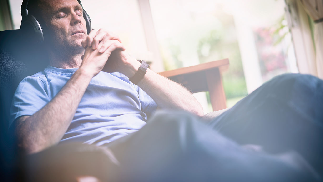 An elderly White man sits contentedly with his eyes closed listening to audio content