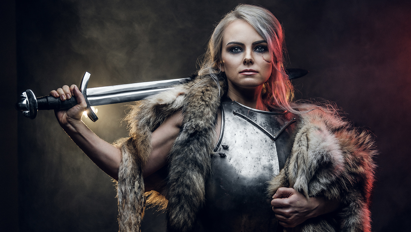 A young woman dressed as a Viking in armor and furs, with a sword over her shoulder