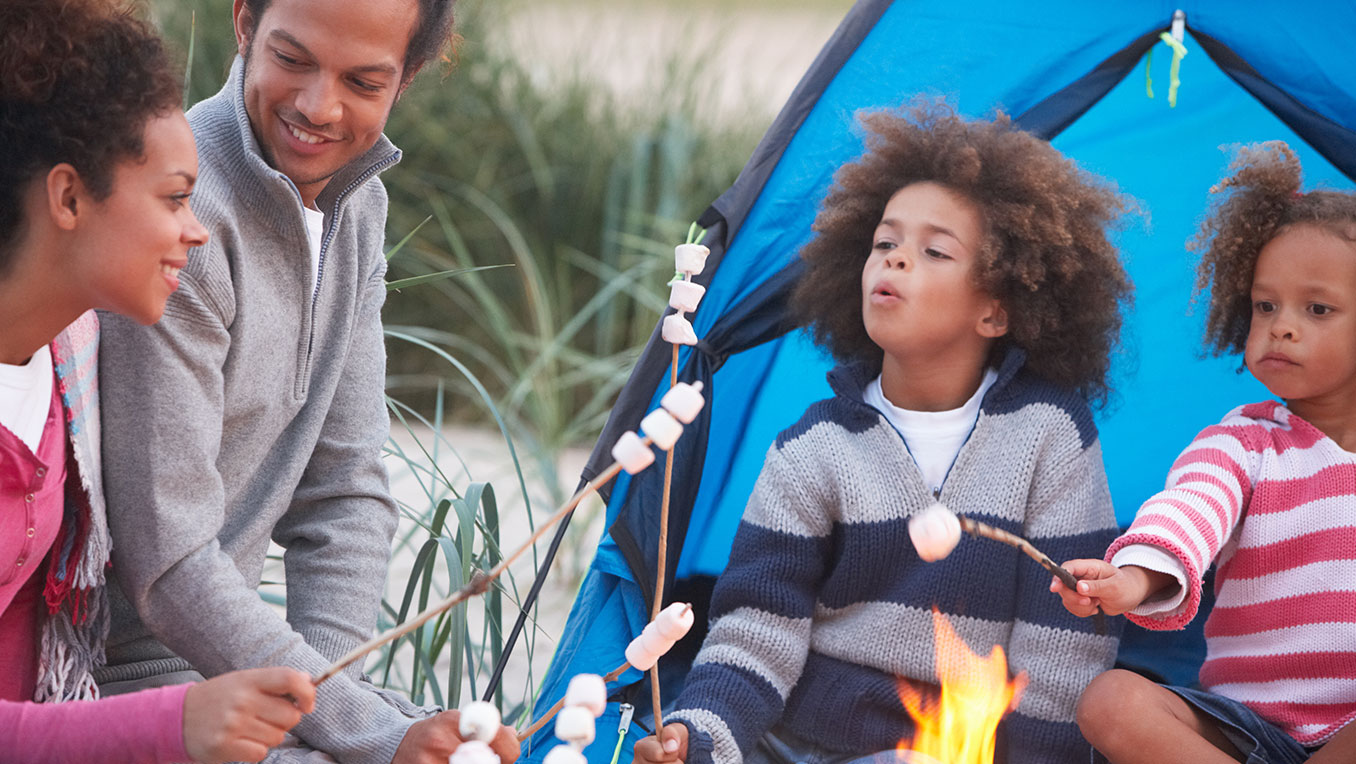 An African American family are camping, roasting marshmallows over a campfire