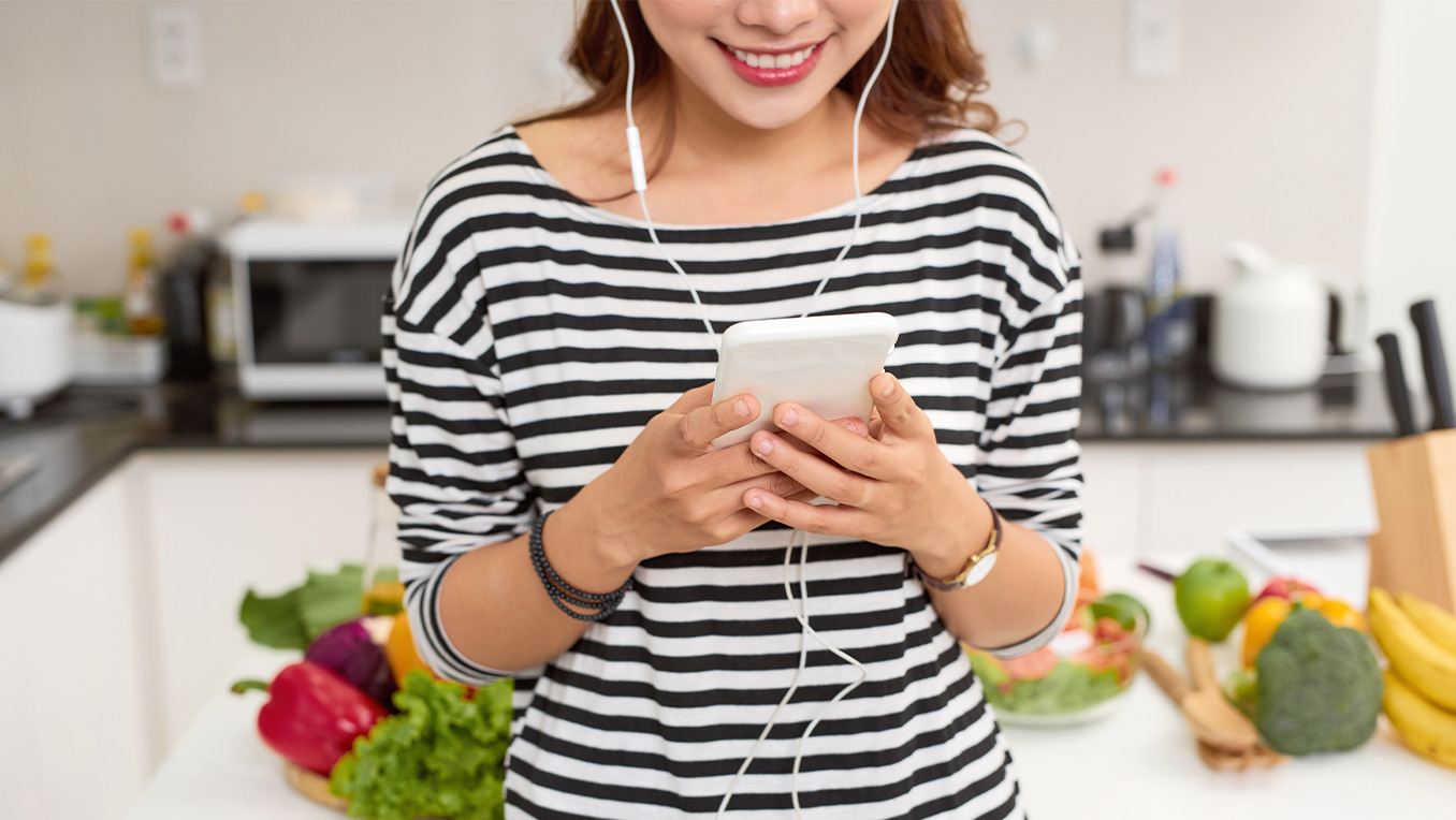 An Asian woman listens to an audiobook on her smart device with earbuds as she stands in front of a vegetable-laden cutting board