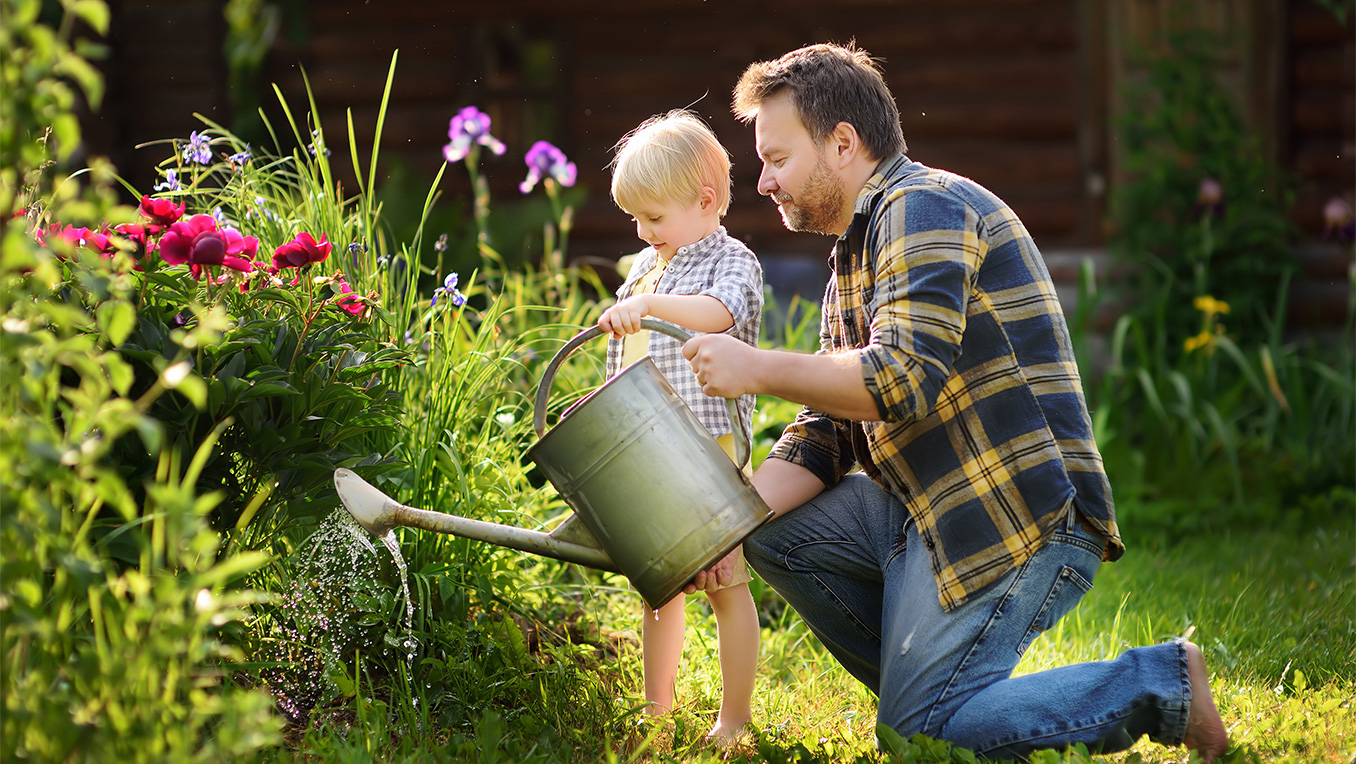A father helps his small sun with a watering can as they care for a beautiful garden.