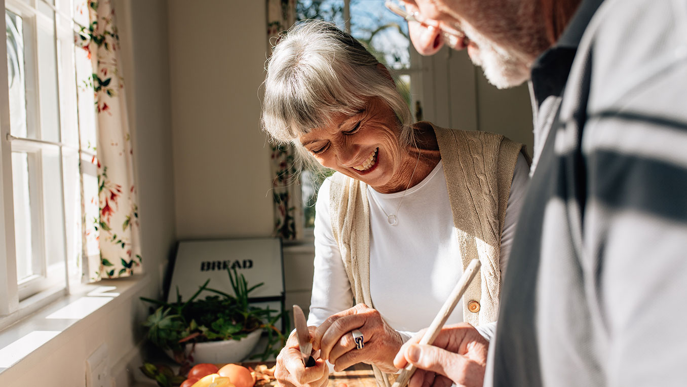 An elderly White couple peels vegetables in a sunlit kitchen, laughing