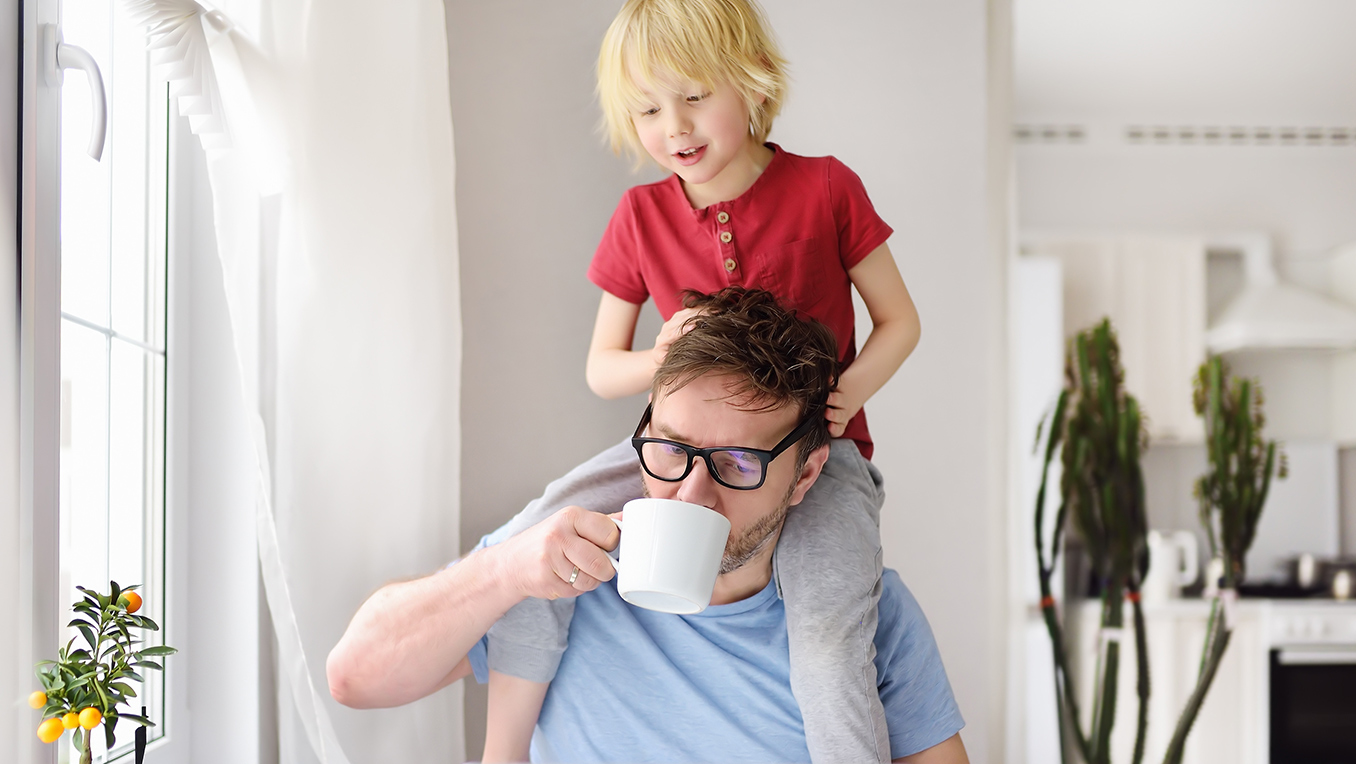 A father sits in front of a laptop computer sipping a mug of coffee while his young son sits atop his shoulders and plays with his hair