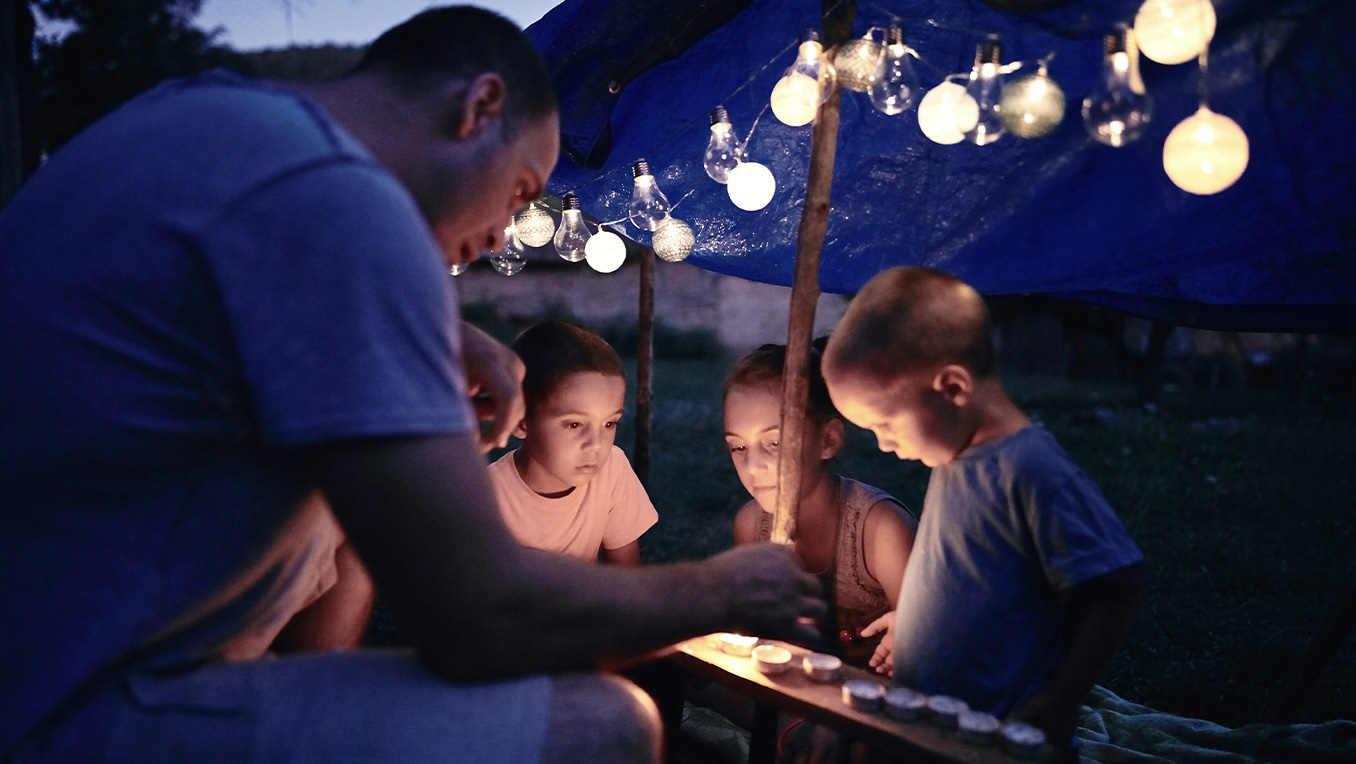 A father lighting candles with his young children as they camp outdoors under a canopy