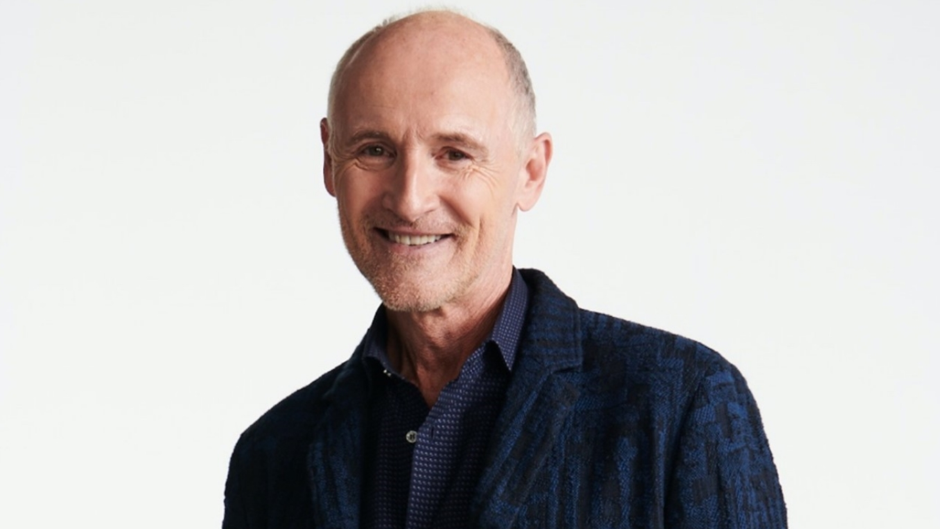 A portrait of Colm Feore in jeans and a navy blazer