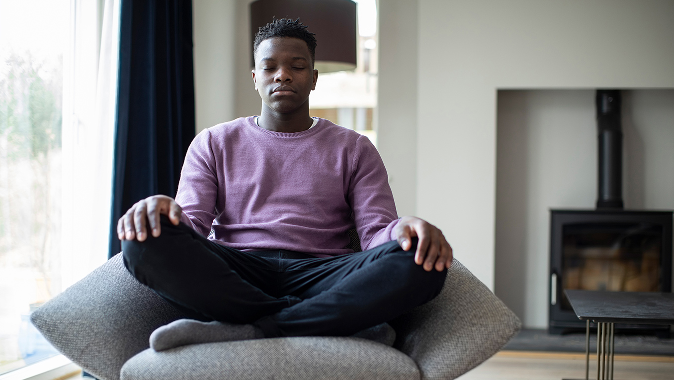 Man sits crossed legged in a chair in his living room meditating wearing a purple sweater