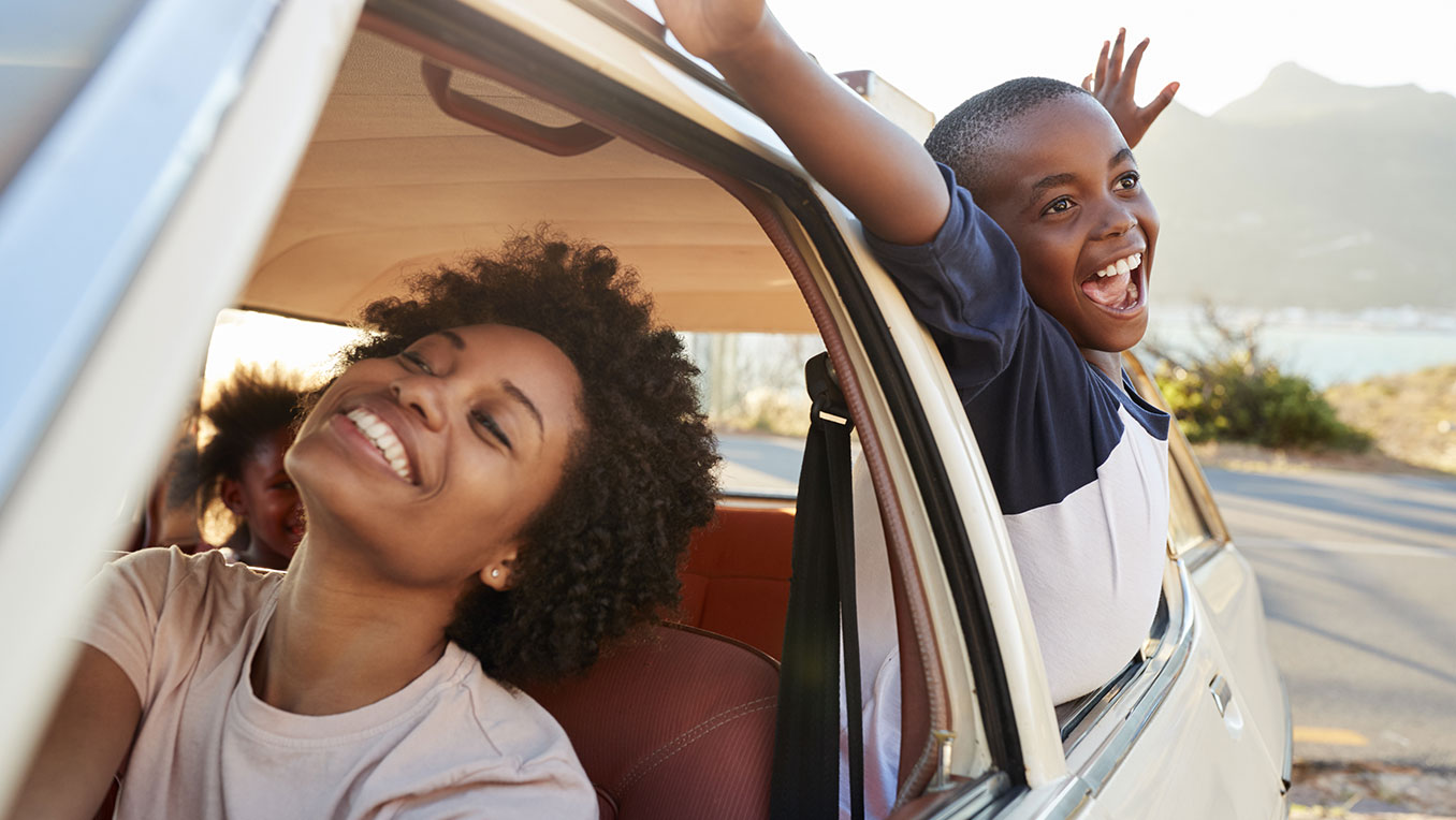 An African American family is on a road trip. The son is hanging out the back window with arms spread, smiling
