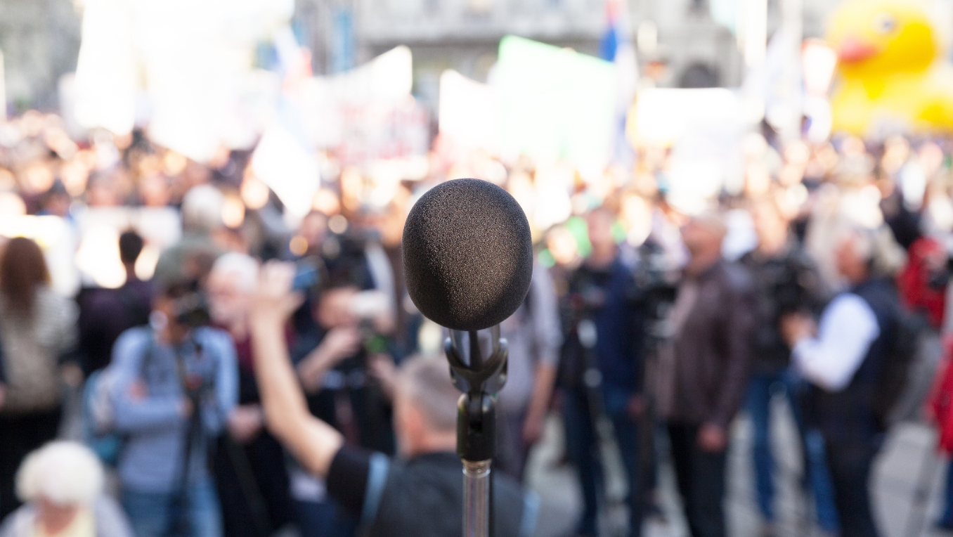 A photo of a political rally with a microphone in the foreground
