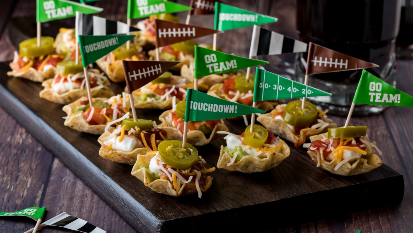 A photo of mini nacho bowls with small sports flags sticking out of them