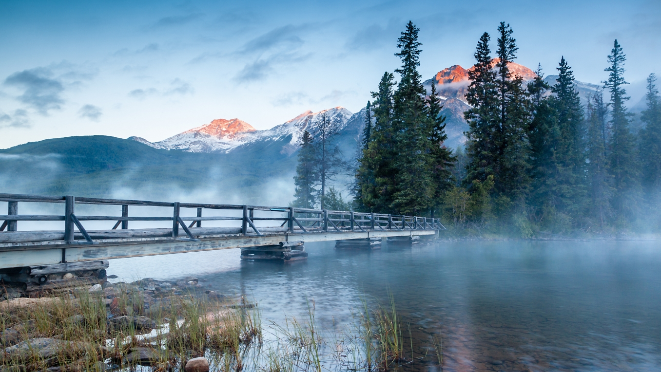 A photograph of morning mist over Pyramid lake in Jasper Alberta