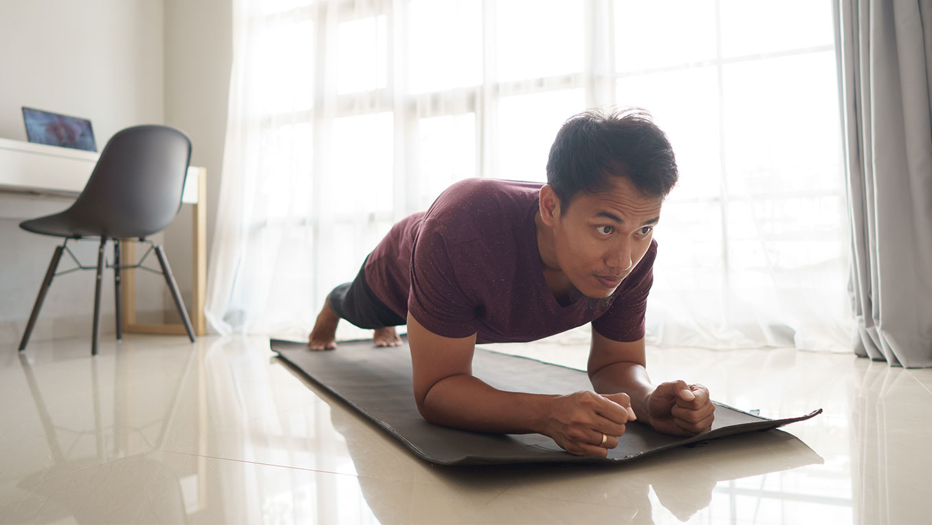 A man is holding the plank position on a yoga mat in a brightly-lit room