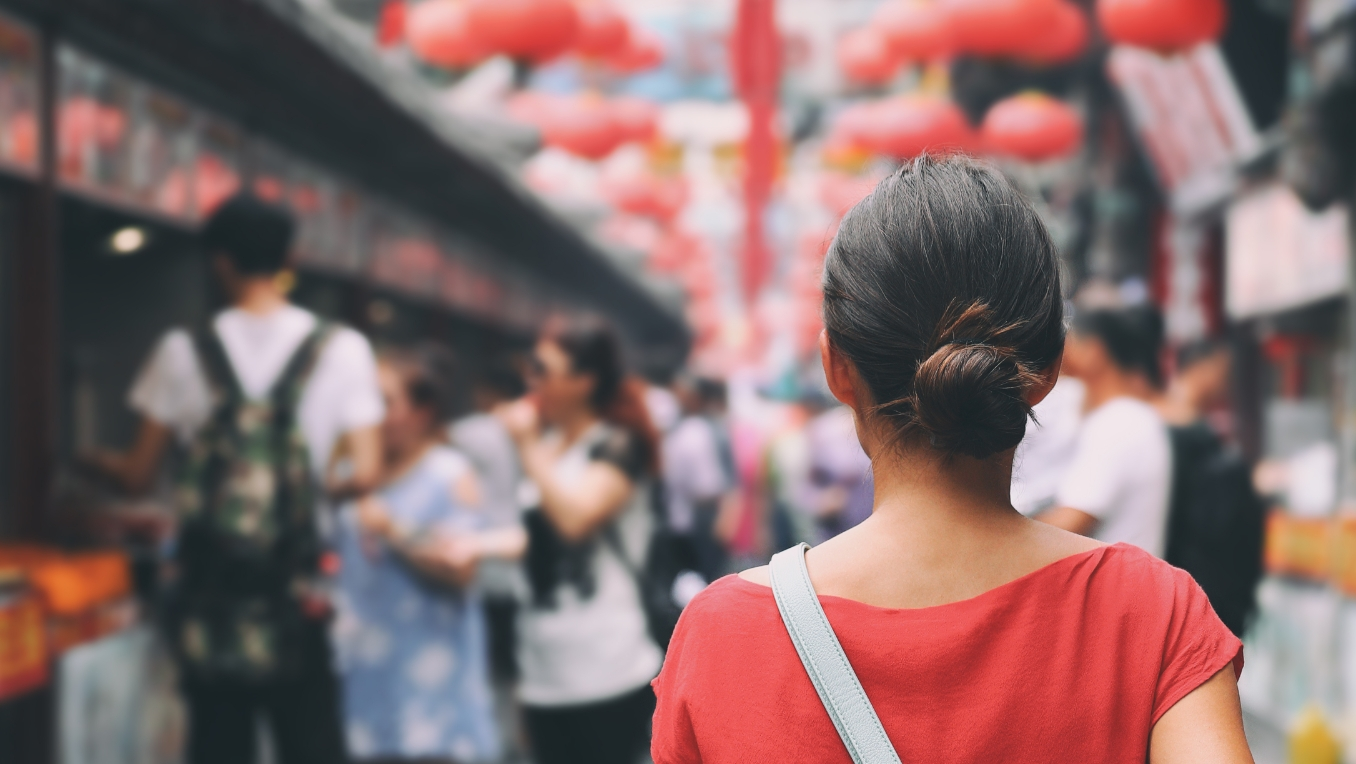 A photograph of a woman walking toward a busy Japanese marketplace