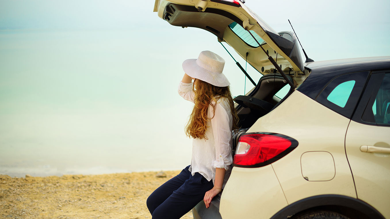 A young White woman in a beach hat sits on the open hatchback of her car on a beach and looks out to sea