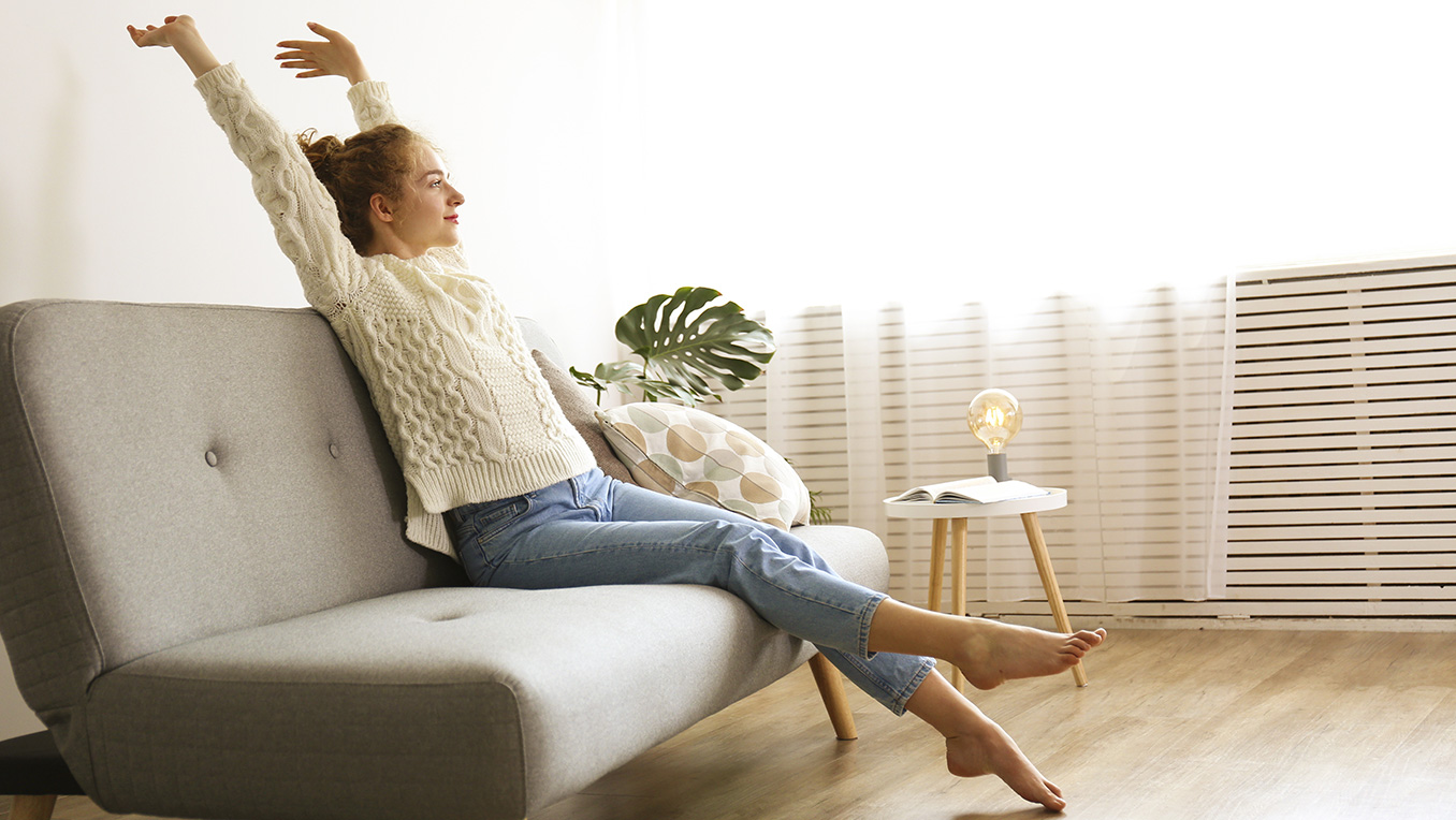 Women wearing a white sweater stretches on a couch sitting in her living room