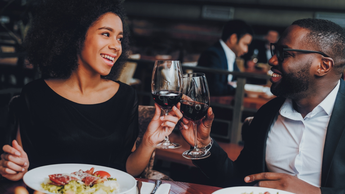 A well-dressed couple enjoys a glass of wine and dinner together