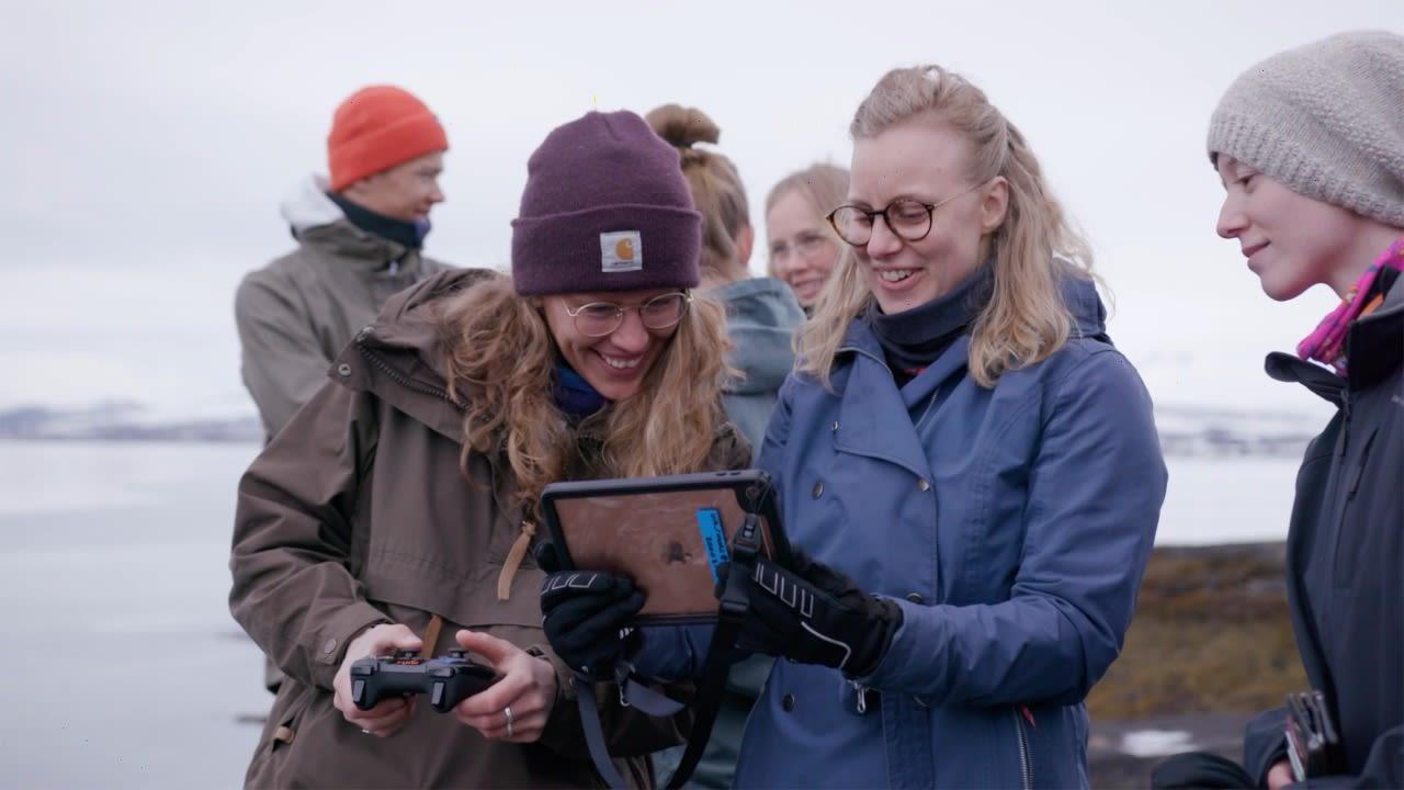Studenter på UiT ser på undervannsbilder fra en Blueye drone på en ipad