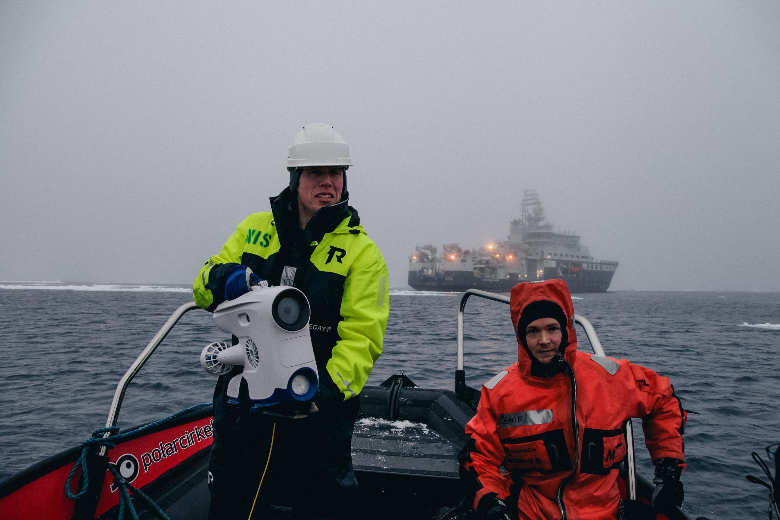 Martin og en av forskerne i en båt sammen med undervannsdronen Blueye Pioneer