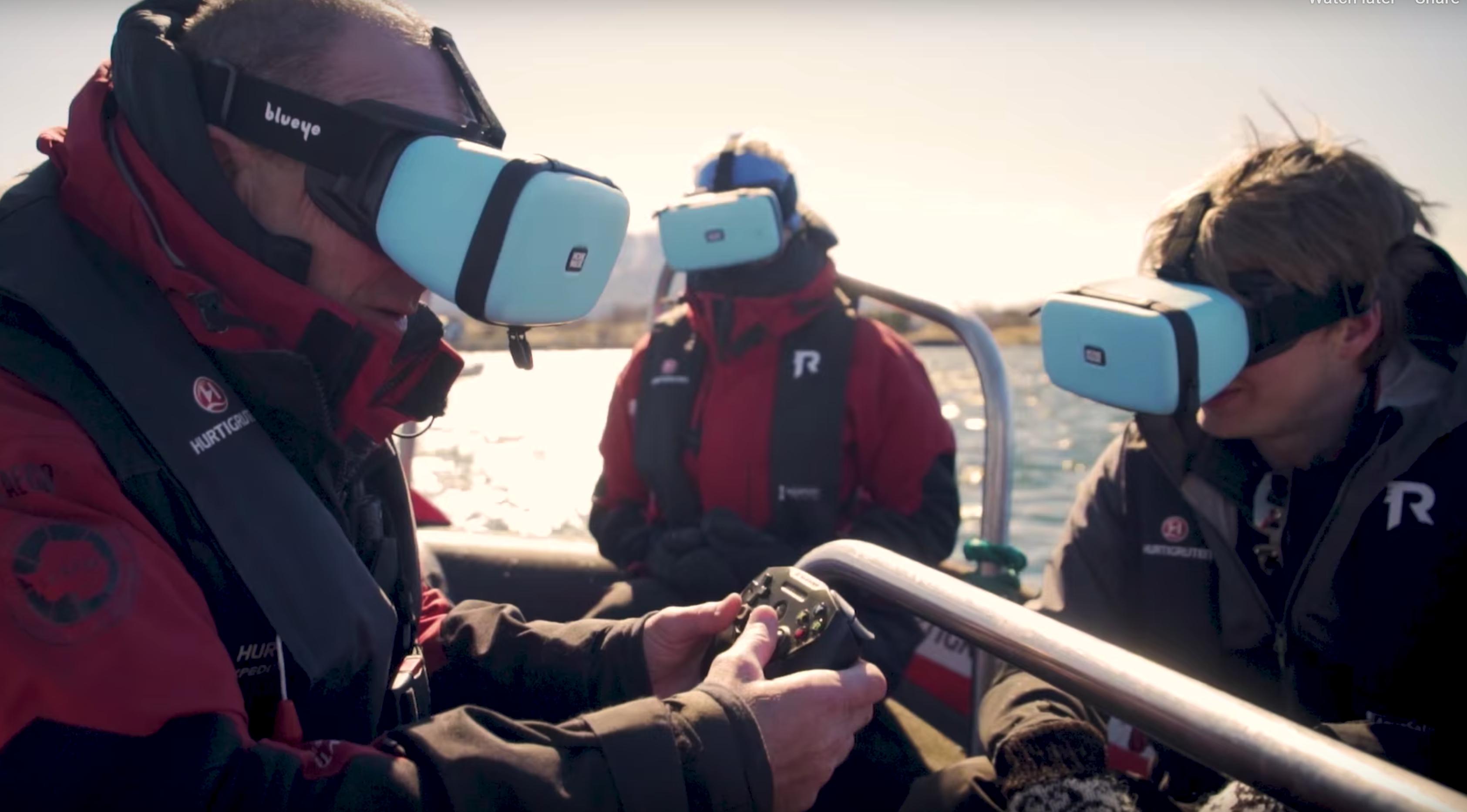 Personer i en båt som nyter live undervannsbilder gjennom en smarttelefon plassert i en MovieMask.