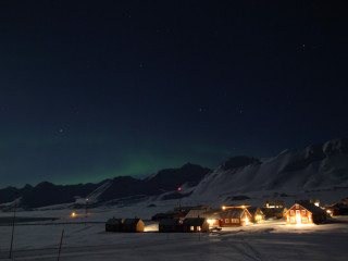 Ny Ålesund with aurora borealis in the background