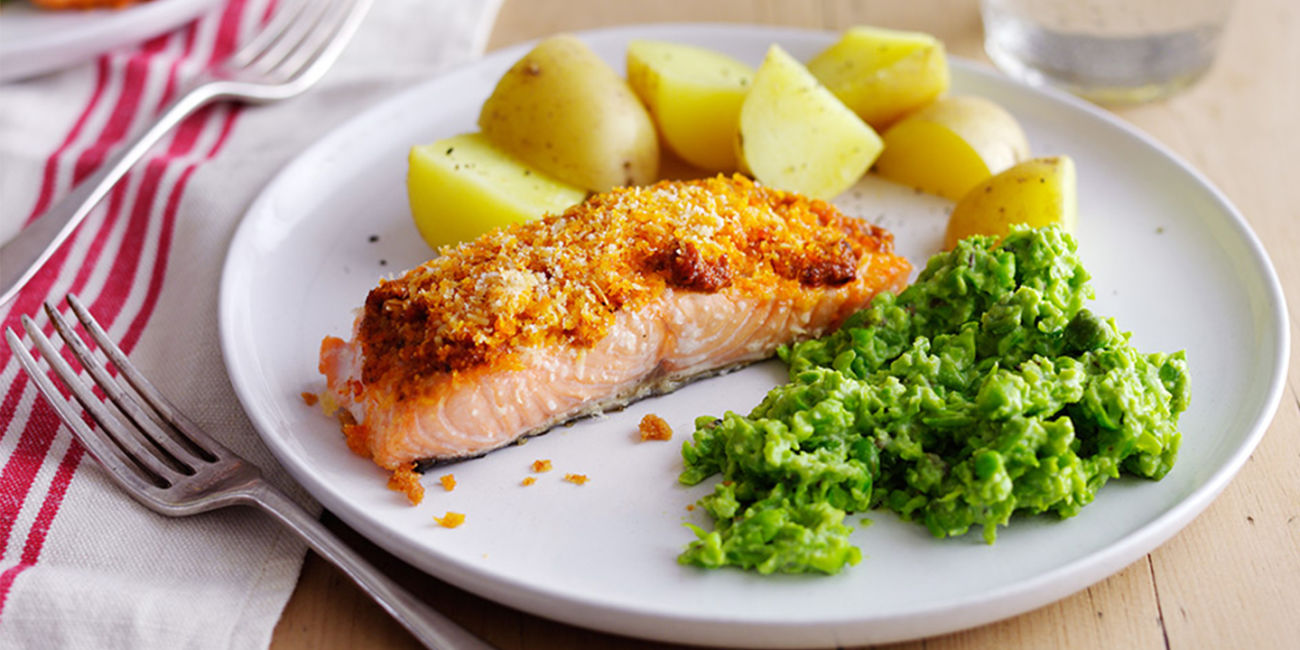 Salmon with pesto topping and herby mushed peas
