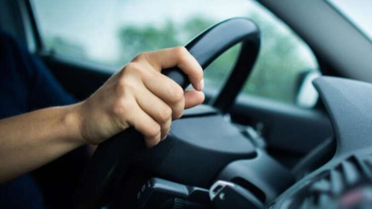 View of car driver holding steering wheel