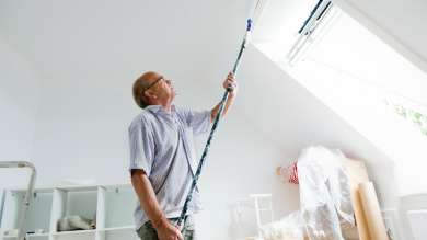 Man painting attic room next to skylight