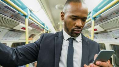 Man in suit looking at phone on the way to work