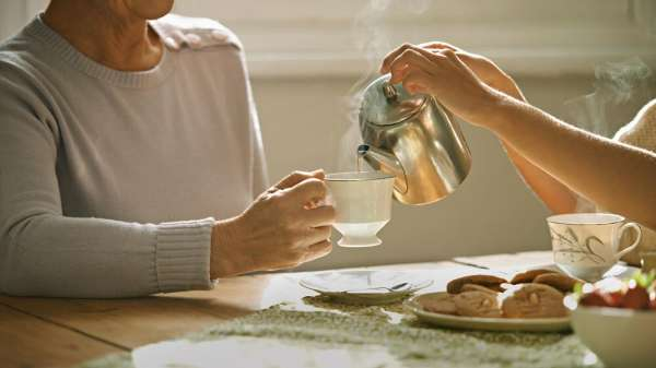 Person pouring tea from teapot