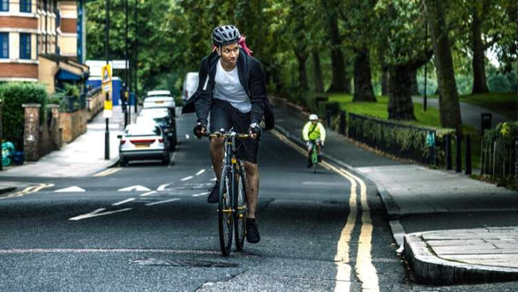 Man on bicycle, cycling along quiet road