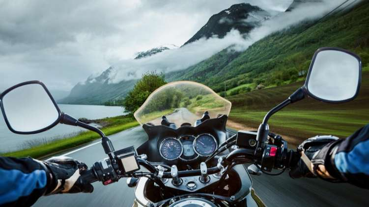 Biker driving a motorcycle rides along remote road. First-person view.