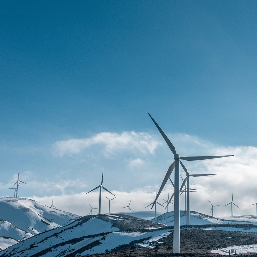 A wind farm spread across snowy mountains