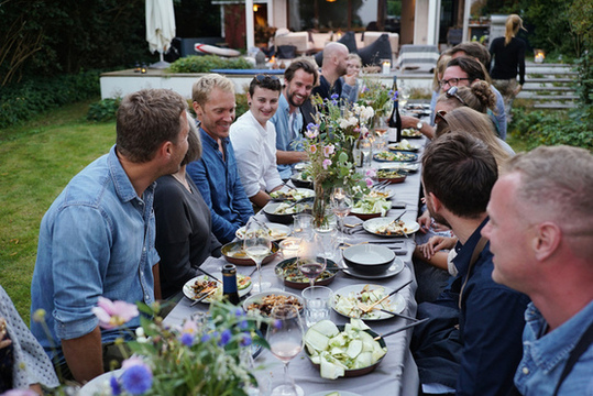 People sitting at long table in garden